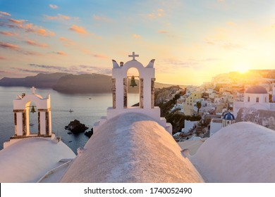 Romantic sunset on famous Santorini island resort. Arch with a bell, white houses and romantic sundown sky in Oia  at sunset, island Santorini, Greece, Europe