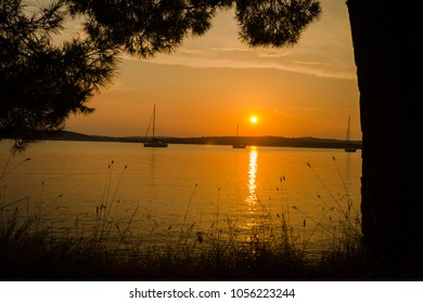 Romantic sunset with orange sky and water reflection in the sea bay
