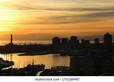 Romantic sunset with panoramic view of Genoa city with its harbour, the silohuettes of skycrapers and the majestic lighthouse (Lanterna) symbol of the Italian city. Genoa capital of Liguria, Italy.