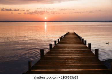 romantic sunset scenery with wooden boardwalk at lake chiemsee, bavaria