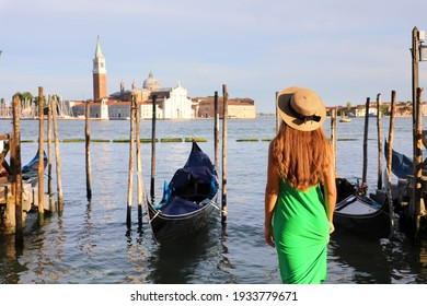 Romantic sunset in Venice, Italy. Back view of young woman admiring Venetian Lagoon.