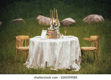 Romantic table with flowers and candles in the middle of the meadow.