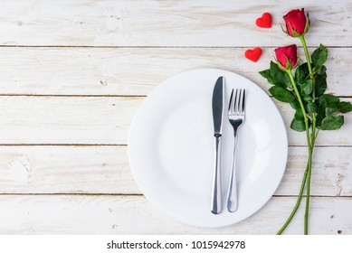 Romantic table Red roses  knife, spoon, plate and hearts on old white wood table/Valentines day background with copy space