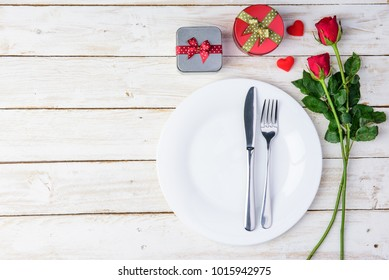 Romantic table Red roses/gift box, knife, spoon, plate and hearts on old white wood table/Valentines day background with copy space