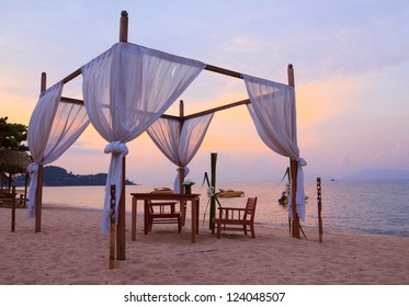 Romantic table setting on the beach at sunset