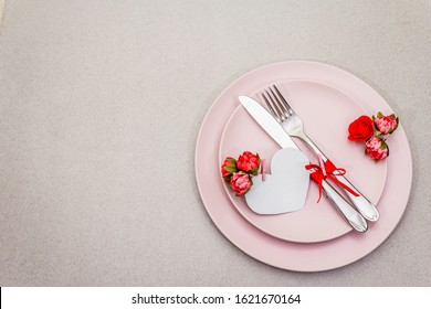 Romantic table setting on light stone concrete background. Valentine's day or Wedding card template. Paper heart, flowers, cutlery, copy space, top view