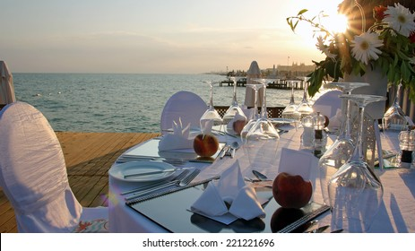 Romantic Table Setting on Pier at Sunset. Luxury wedding reception by the sea.  Wedding table with a beautiful sea view.  Wedding reception place ready for guests.