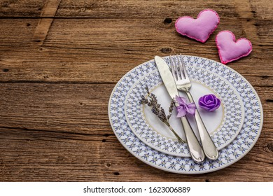 Romantic table setting on vintage wooden boards background. Valentine's day or Wedding card template. Lilac felt heart, lavender, rose flower, cutlery, copy space
