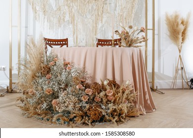 Romantic table setting in a restaurant for a holiday. Wedding decor for newlyweds at a banquet. Dried flowers floristry and candles, boho style. Cartering service for the bride and groom and guests.