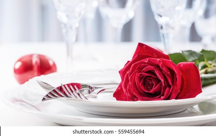 Romantic table setting for two with red roses plates cups and cutlery.