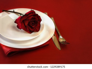 Romantic table setting for Valentines day or dinner date celebration wedding restaurant . Valentines day table setting with red rose bud, white plates, fork and knife on red tablecloth background.