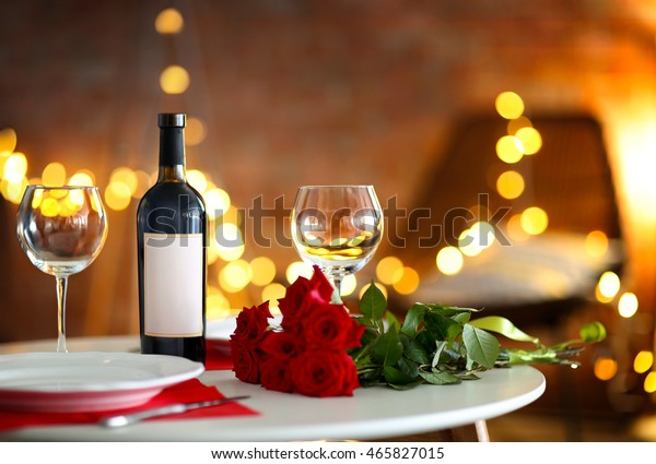 Romantic table setting with wine and beautiful roses on blurred background