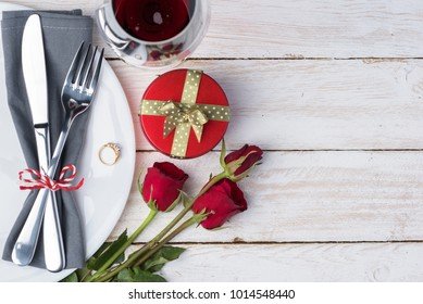 Romantic table for Valentine's Day with fork, knife, napkin, plate, ring, gift box, ros and wine glass on old white wood background. with copy space