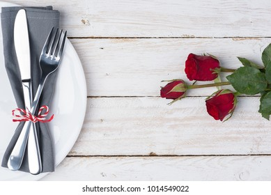 Romantic table for Valentine's Day with fork, knife, napkin, plate and rose on old white wood background. with copy space