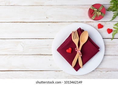 Romantic table for Valentine's Day with wood fork, spoon, plate, gift box and hearts on old white wood background. with copy space