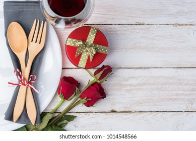 Romantic table for Valentine's Day with wood fork, spoon, plate, napkin, gift box, rose and wine glass on old white wood background. with copy space