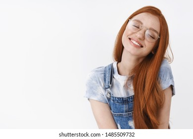 Romantic tender dreamy redhead girl tilt head close eyes and smile joyful, dreaming, fantasizing about cute things, recall nice cheerful memories, stand white background delighted silly