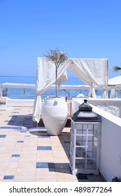 romantic terrace patio of seaside resort with outdoor furniture, flower bawl and sea view, Crete, Greece. Selective focus