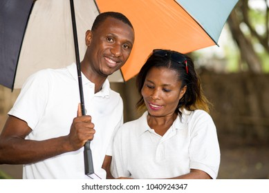 romantic tourist couple standing outside holding hands under a colorful umbrella