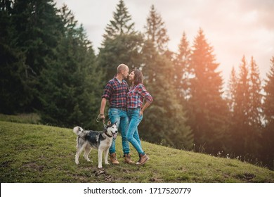 Romantic traveling couple walking with husky dog in the mountains. Caucasian man and woman in love in mountains at sunset. Portrait of a happy couple smile to camera. Lifestyle concept. Banner
