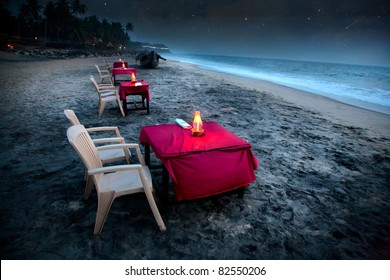 Romantic tropical cafe on the beach near the ocean. Tables with pink covers illuminated by candles and stars falling at night sky background