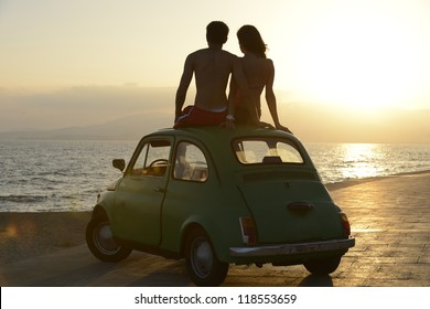 romantic vacation: couple at sundown on the beach with car