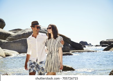 Romantic vacationing couple strolling on beach, smiling