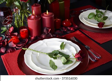 Romantic Valentine Candle Light Dinner for Two Table Setting for two with red roses, gift and burning candles against a black background.