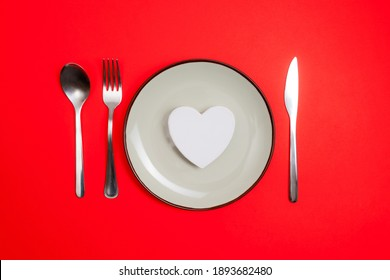 Romantic valentines day dinner idea concept. Heart on plate and silver wear on red background.