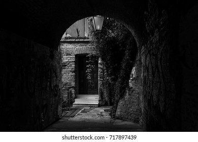 Romantic view on beautiful overgrown house at the end of an arched passageway, black and white
