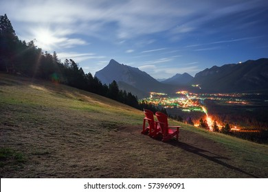 A romantic viewpoint with a pair of red chairs atop a grassy mountain slope, overlooking the town of Banff under a moonlight night sky.