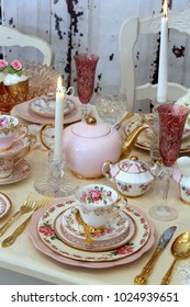 Romantic vintage pink and gold table for two - tea cups, plates, gold cutlery flatware, champagne glass, teapot, candles on rustic white wood table - high tea party