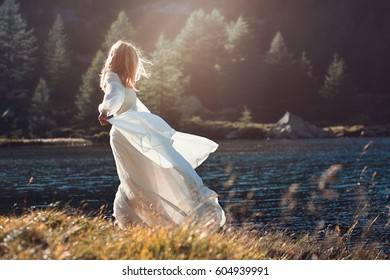 Romantic vintage woman in sunset light. Alpine lake background
