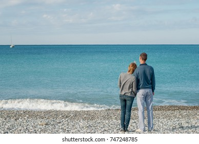 Romantic walk - unidentified man and woman in casual clothes hold hands and look at the sea on boat floating away on summer day
