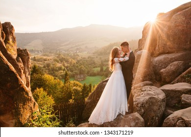 Romantic wedding couple of groom and bride hugging and kissing while standing on the top of the cliff in national park with beautiful view on sunny summer day. Sun rays