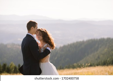 Romantic wedding couple posing on top of mountains at sunset with amazing view. Beautiful newlyweds on their wedding day
