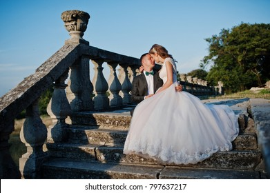 Romantic wedding couple sitting on the stairs next to the castle.