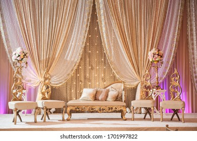 Romantic wedding decor with lit candles, elegant furniture, lush floral arrangements and inviting uplighting.