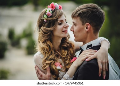 Romantic wedding moment, couple of newlyweds kissing portrait looking at each other in nature in the park. Wedding ceremony.