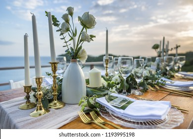Romantic Wedding Table Top Layout Table Spread no people tropical location with gold cutlery and scenic view of sunset with copy space