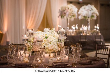 Romantic Wedding Table Top Layout Decor with large lush floral bouquets including white roses, ranunculus, persian buttercups, white orchids and candles
