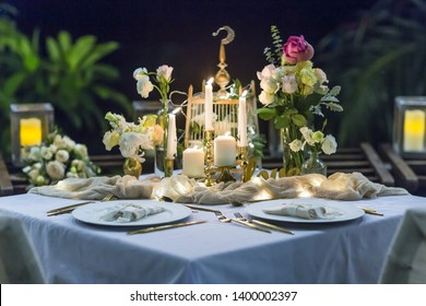 Romantic Wedding Table Top Layout Table Spread no people tropical location with gold cutlery at night evening event