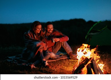 Romantic Weekend. Couple In Love Near Camping In Nature. Portrait Of Lovely Happy Man And Beautiful Woman Hugging And Resting Near Bonfire On Vacation Outdoors. High Quality Image.