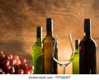 Romantic wine tasting atmosphere in a winery cellar with an empty wine glass in front of red grapes and wine bottles on a wooden background, closeup shot with blurry low depth of field