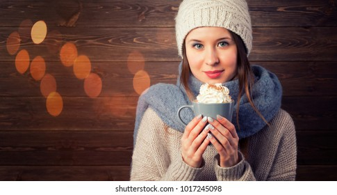 Romantic Winter Hipster Girl in Knitted Sweater and Beanie Hat Enjoying a Cup of Hot choclate in Hands. Lovely Dreaming Woman. Warming Up Concept. Toned Photo with Copy Space.