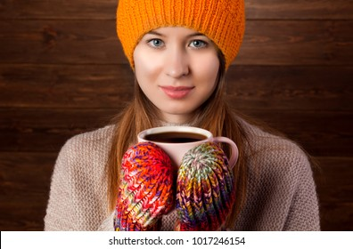 Romantic Winter Hipster Girl in Knitted Sweater and Beanie Hat Enjoying a Cup of Hot Tea or coffee  in Hands. Lovely Dreaming Woman. White Brick Wall Background. Warming Up Concept.
