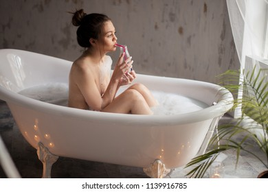 romantic woman with bottle of juice in the bathroom