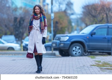 Romantic woman in coat and scarf walking around the city