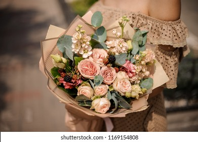 Romantic woman in dress holding a nude beige bouquet of flowers wrapped in craft paper