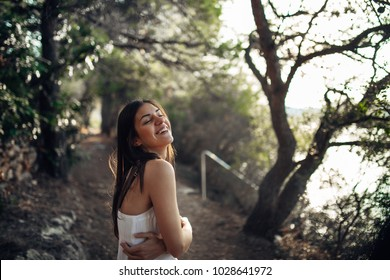 Romantic woman enjoying walk in the nature on a sunny morning.Mindful carefree female in natural environment feeling stress free and relaxed